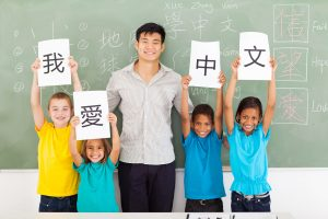 21191566 - friendly male chinese teacher with group multiracial primary students holding papers saying i love chinese