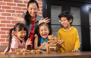 Happy Asian Kids and their teacher are playing wooden blocks stack game in classroom at the school together. Falling. Laughing.